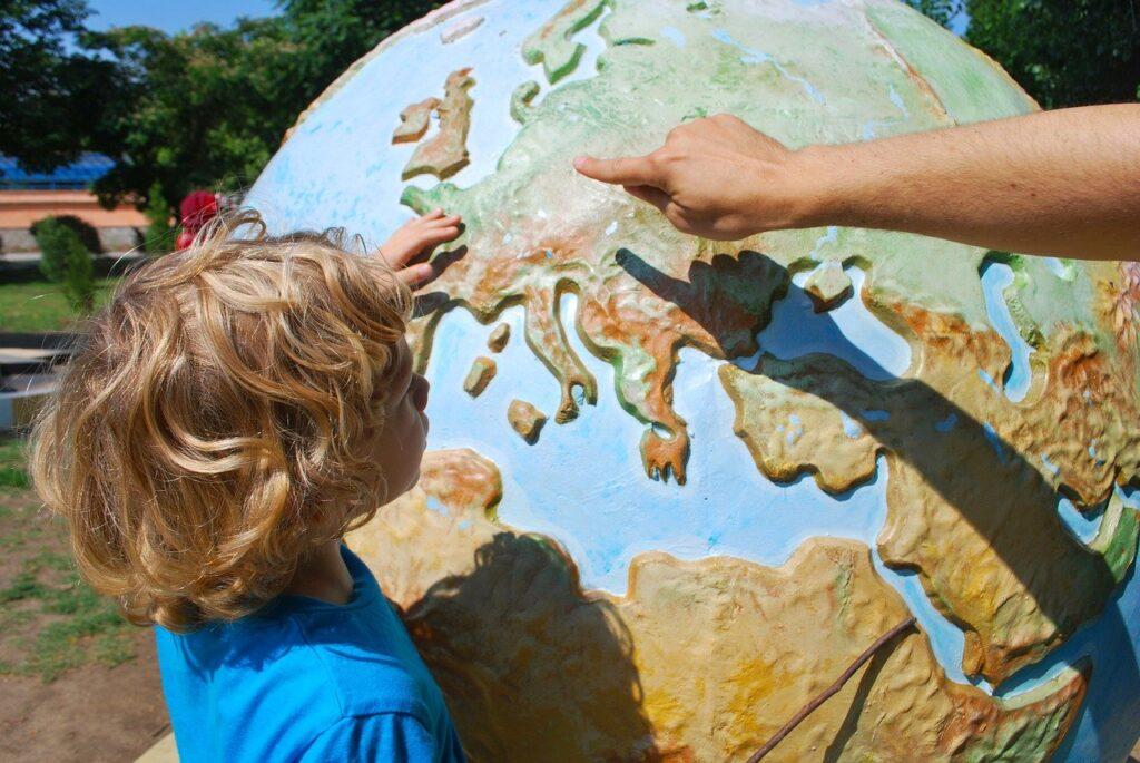 Teacher showing a child a world globe